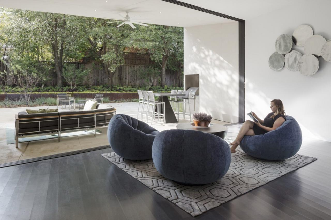 living area with round, gray chairs near a glass wall