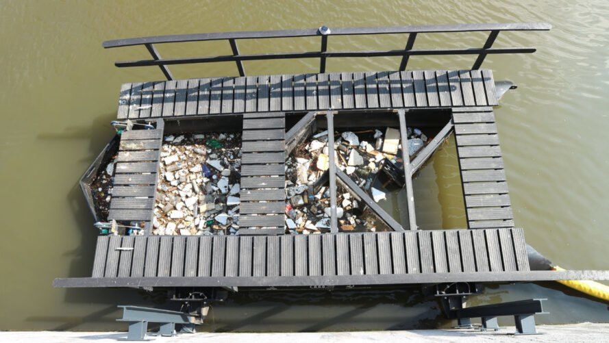 floating waste trap collecting plastic from a river