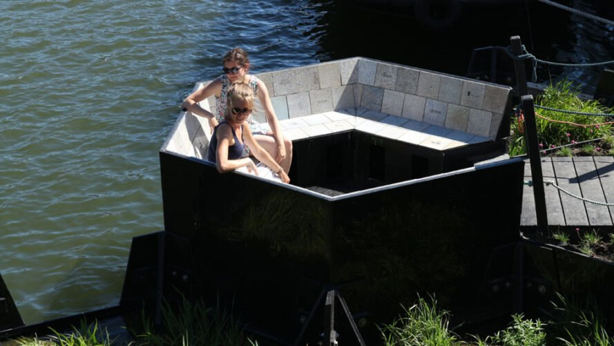 two people sitting on a floating bench