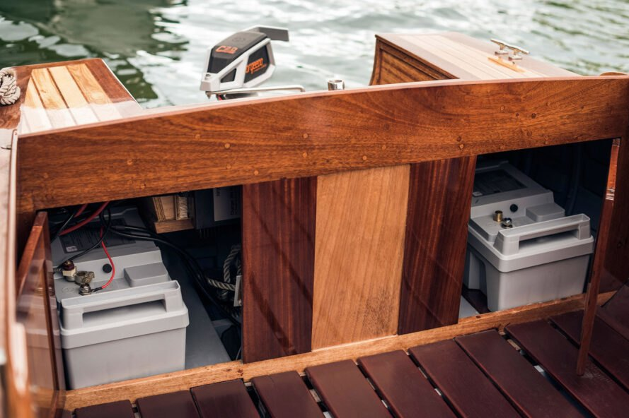 a wooden boat with electrical motor components in a compartment towards the back of the boat