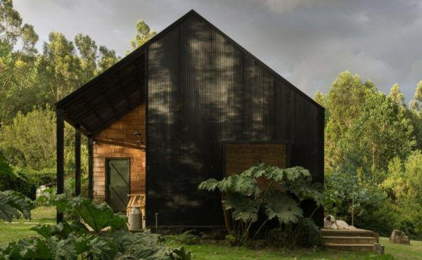 black gabled home with small, light wood porch