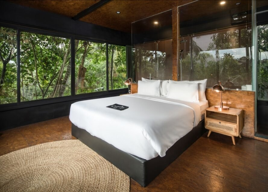 large white bed in room surrounded by windows