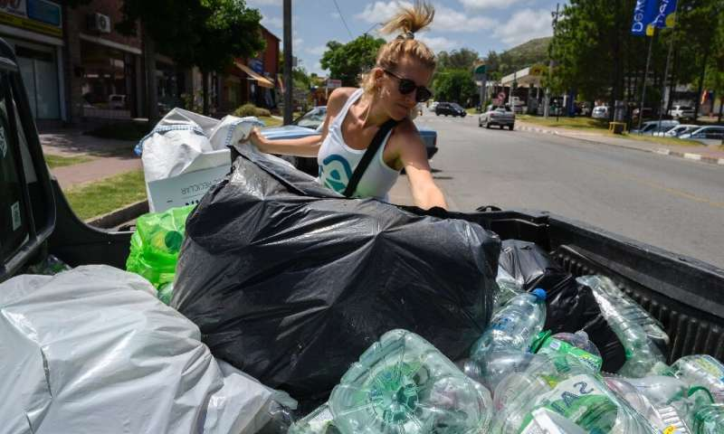 "Nicole Wyaux, co-founder of the ""Plasticoin"" project, fills up a container with plastic waste in Piriapolis, eastern U"