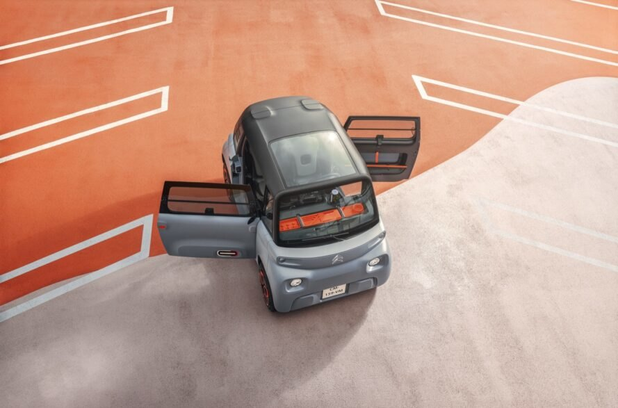 aerial view of tiny gray electric car with open doors