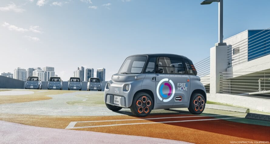 tiny gray electric car with logos on the door